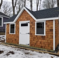 10x16 New England Colonial With Upgrades 1/2 Moon Gable Vents Diamond Plate on All Doors Dormer With Single Door and Transom In Dormer Transom Windows above Double Door Cedar Shake Siding with Stain